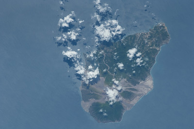 Caption by Space Station Academy student: This image shows the island of Basse-Terre in the Caribbean Sea. The island contains green spaces signifying trees or vegetation with what appear to be rocky and barren surfaces. In the southern portion of the island appears to be smoke is a concentrated cloud over what appears to be an elevated location.