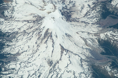 Caption by Space Station Academy student: This image shows the condition of Mount hood in northern Oregon. This is a snow capped peak with a solid covering of snow and ice. It would appear to be difficult to climb so proper precautions should be made for that type of activity. There is some barren land in the right portion of the image before you reach the green forested area again.  This could be one in a series of images taken over time to monitor the image of climate change by seeing if the snow or ice has receded. There may be signs of this on the right portion of the mountain image. This image also shows that this area is protected or should be as their is no visible signs of a permanent human presence.