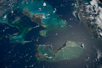 Caption by Space Station Academy students: This image shows the Bahamas island chain off the Florida coast. There is a difference in the color of  the water as the water nearer the islands is more greenish in color and the ocean water farther away is a darker blue. There is a solid large land mass to the right of the picture which might be Florida. It is hard to tell with the cloud cover. some of the smaller consistent white spots on the land mass to the right might represent a city such as Miami.