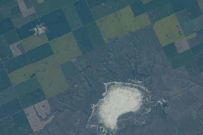 "Caption by Space Station Academy student: This is a picture of farmland in Southwest Canada between Hanley and and Davidson.  The different patches of green are different pastures or farmlands.  I'm still trying to figure out what the ""blog"" of water is, but I think it's a lake near Rt 11.  I like seeing how all the different colors of farmland go together. I like what looks like a ""blob"" of water, it looks like sea foam. I picked this picture because I really liked how all the different colors of land looked like different horse pastures."