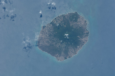 Caption by Space Station Academy student: This is a direct top view of an island in the Caribbean. There is a mountain in the middle of the mountain, possibly a volcano. There are cities/towns in some parts of the island. I was curious about this island and where it was. I thought at first it would be one of the islands of Hawaii, because most of those islands appear similar, with a volcano in the middle and towns near the edge. I learned that this island is called Nevis, and is a nation with St. Kitts.