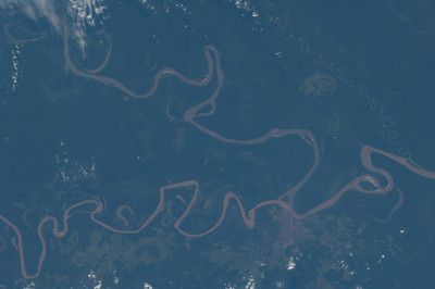 Caption by Space Station Academy student: This image shows the junction of the Madre de Dios and Beni rivers near Riberalta, Bolivia in South America. The Madre de Dios River joins with the Beni River in northern Bolivia and continues through Brazil as a tributary of the Amazon River. Rich greens along the river show the rainforests with one city (Riberalta) where the rivers meet.  The curving river supports lush rainforests and diverse wildlife. The sharp contrast of the river's brown, whimsical trail through the land's rich green makes this image strikingly beautiful.