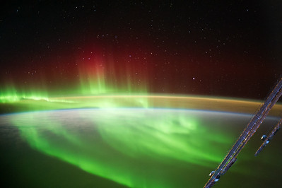 Caption by Space Station Academy students: 1) This is a picture of the Aurora Australis or Southern Lights.  You can see the lights of all different colors dancing up and down and you can also see part of the space station.  Beyond that you can see the thin atmosphere of Earth.  The white color underneath the lights is snow and you can see a little bit of blue and that's the melted snow.  You can see the Southern Lights dancing up and down.  I like how it seems like the lights are having a contest to see how high they can go.  I also think it's cool that you have a pretty good view of the Earth's atmosphere.   It's very thin and the lights seem to go through the atmosphere.             2)  It looks as if the sun is rising and the northern lights are still going and finishing up for the night. There is a beautiful reflection off of the atmosphere and a the beautiful green northern lights. 3)  This image is the Aurora Australis or southern lights, the southern hemisphere's version of Aurora Borealis. Not only do the green lights swirl majestically and become red as they retreat from Earth, but the stars can be seen as well as the horizon of light, creating a spectacular visual array of colors set off by the night sky on one side, the earth on the other.  4) This photograph was taken at such an angle as to capture both the earth below and the stars above. There is a powerful otherworldliness in seeing the night's sky as one would see it from on earth, the earth itself as seen from space, and the stunning light show in between  5) The aurora is a beautiful and benign aspect of more dangerous space weather.  Space weather must be monitored for the safety and health of astronauts, to protect satellites and Earth's power grids. The space perspective helps people better understand Earth's relationship with the sun.