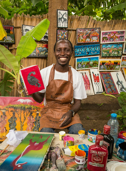 Lake Manyara, Tanzania: Sulieman, a member of a local Tinga Tinga art collective; their paintings hang on the fences and lean against the trees in the banana grove that serves as their gallery.