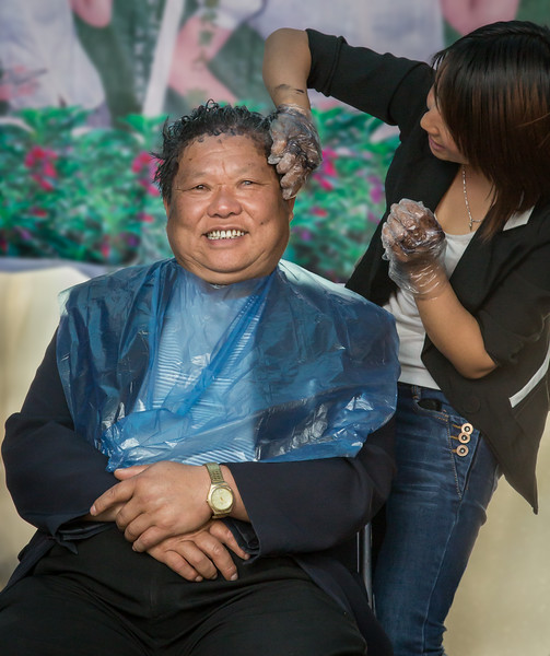 Dali, China: an attendee at the Third Month Fair gets his hair dyed.