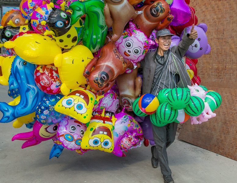 Dali, China: a balloon vendor offers his wares at a Third Month Fair, the largest annual gathering of the Bai minority in Yunnan.
