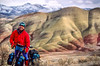 Winter bike tourer on dirt road in Oregon's John Day Fossil Beds Nat'l Monument - 72 ppi 1