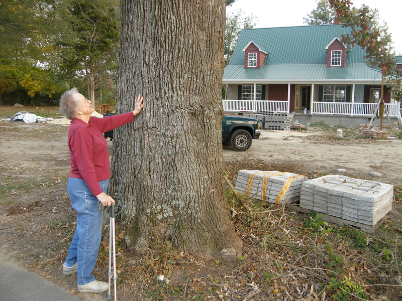 And here she is at the foot of that same tree, 63 years later. The Nelson homestead house was gone by then, but the tree remained.
