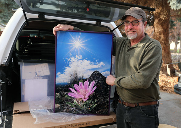 Standing in front of his pickup fully loaded with prints, Steve Slocomb prepares for yet another show of his unique sunburst flower photographs that have captured the imagination of many people this past year.