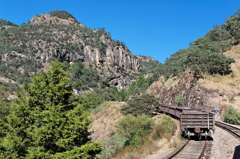 Seemingly abandoned freight cars in a nice canyon setting.
