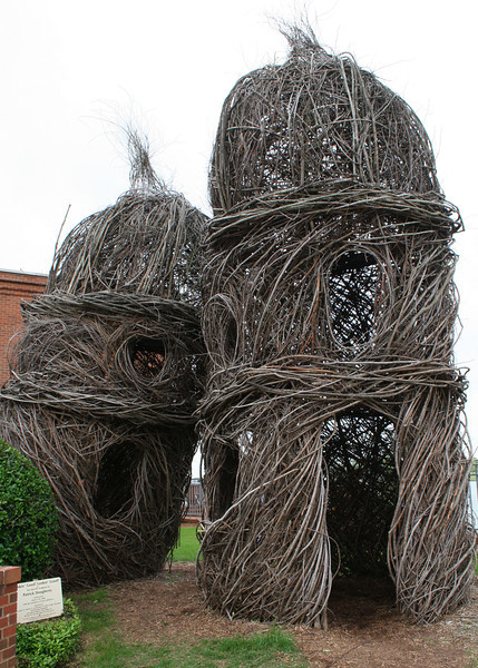 """Patrick Dougherty has made about 200 site-specific sculptures from saplings over the past two decades. He has worked in museums, parks, and gardens around the world to create temporary art that often resembles children's tree forts, bird's nests, and primitive dwellings. He says, """"You get one great year, and one pretty good one"""" from his sculptures. Once they begin to deteriorate, they are removed and destroyed, often by composting.<br /> <br /> To title the work at the Montgomery Museum of Fine Arts, in Montgomery, AL, the artist chose an expression repeated by the museum's chief of security, who ambled around the site throughout its construction, """"Lookin' Good, Lookin' Good"""".  Once he harvested the 140 big sticks that he set in two-foot deep holes in the ground, he decided to try something he had not done before - to make the domes from the ends of those sticks (the extended branches) rather than by adding short sticks. Due to the design, materials, and volunteer assistance (approximately 1000 work hours total), the result is a unique, one of a kind observation by the artist that initiates a visual dialogue with the museum building."""