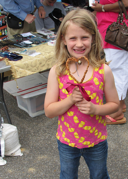 Jean set up a table where young and old alike could learn how to make hearts with pine needles.  Here is a young lady who has just finished making hers.