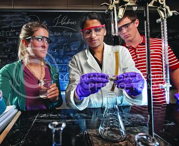 Freshmen Caroline Patelli, left, and Alex Ackley, right, watch graduate student Sarika Rajaleksmi Devi in a chemistry lab. (Photo by John La Barge)