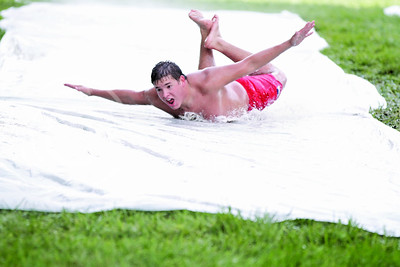 Freshman Daniel Staab glides on a plastic water slide in front of Haymaker Hall. Nine out of ten freshmen choose to live in organized group housing at K-State.(Photo by Jeff Tuttle)