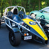 Ariel Atom - a genuine race car that is street legal.  Because of the lack of a windshield it's generally licensed as a motorcycle and the driver is required to wear a helmet.