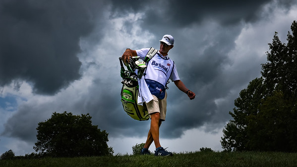 Will Gordon's caddie heads to the 10th tee to begin their round with the threat of bad weather hanging over his head.