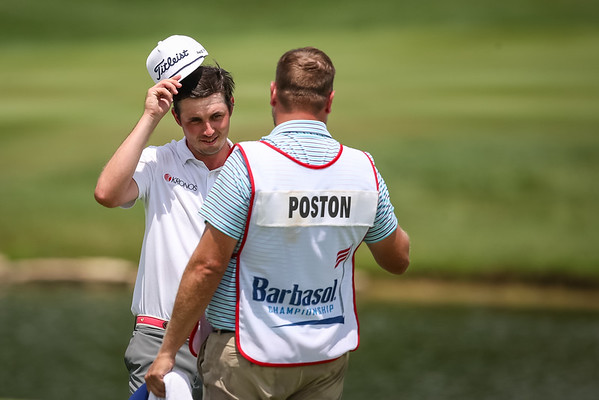 JT Poston celebrates with his caddie after making a birdie on 18.