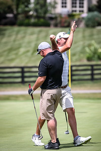 Case Cochran and Randy Hubley celebrate after making a birdie putt.
