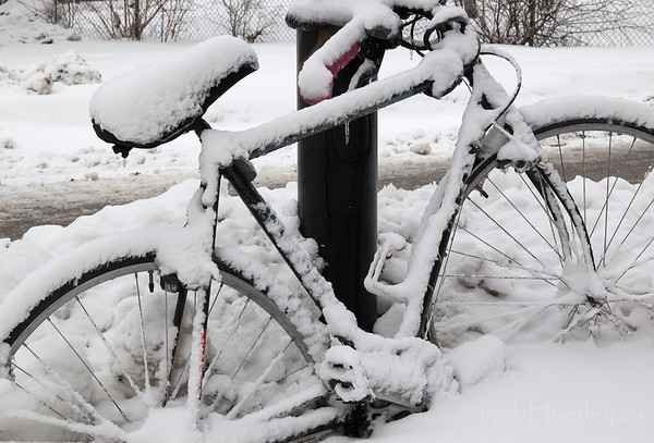 Bicycle abandoned in the storm. A bicycle chained to a post has been abandoned, perhaps temporarily, until the snowy weather passes.  © Rob Huntley