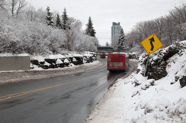 "Buses entering The Ditch.   Section of the Bus Transitway, locally referred to as the ditch, especially during the construction period. This is taken at the Dominion Transitway Station where buses enter ""the ditch"" from the Ottawa River Parkway. It looks like a snow plow has had some affection for the street sign.  © Rob Huntley"