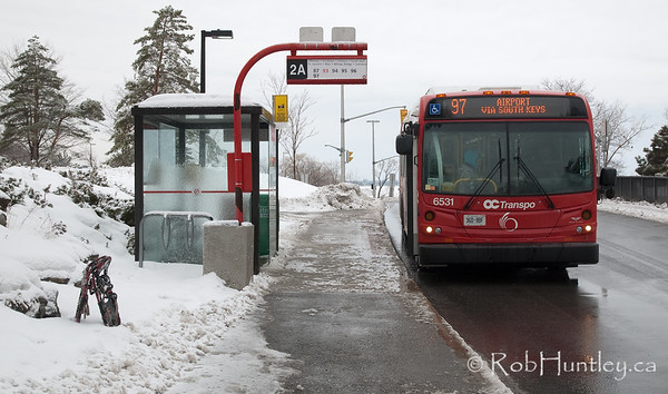 Snowshoes and the Airport Bus - Planned Escape.  I can relate to this. The story says - someone has abandoned their snowshoes at the Airport Bus bus stop. Next day - beach chair in the Caribbean.  (In actual fact, I just took them off before crossing the road and planted them to the side to take a few pictures. I didn't realize I had included them in this shot until reviewing my days take at home).  © Rob Huntley