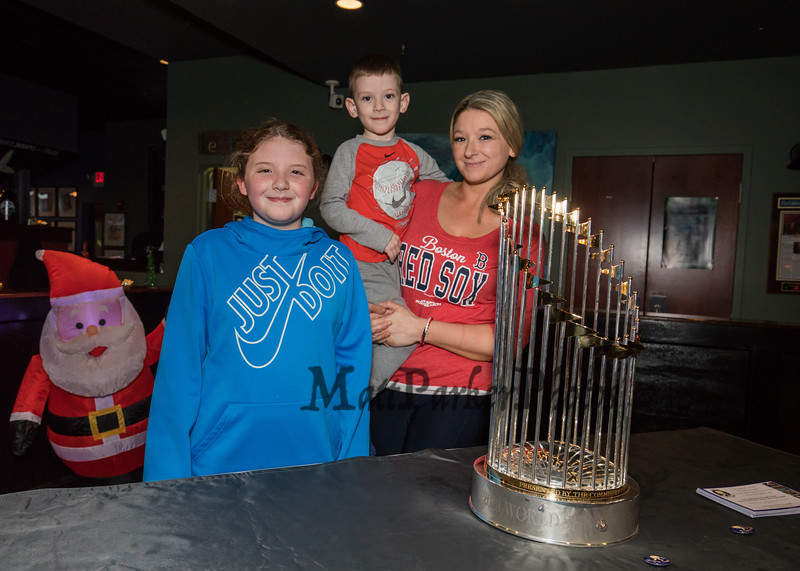 Ashley Barry of Hampton with her kids 5th grader Eva and pre-schooler Landon pose for a photo next to the 2018 Boston Red Sox World Championship Trophy sponsored by The Community Oven of Hampton in conjunction with Amy's Treat a Dover based 501©3 charity to raise money for cancer patients in the Southern NH and Eastern Maine areas on Thursday 12-6-2018 @ Hampton, NH.  [Matt Parker/Seacoastonline]