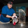 Amesbury Mass. resident Joe Fishwick with his 11 week old son Joe pose for a photo next to the 2018 Boston Red Sox World Championship Trophy sponsored by The Community Oven of Hampton in conjunction with Amy's Treat a Dover based 501©3 charity to raise money for cancer patients in the Southern NH and Eastern Maine areas on Thursday 12-6-2018 @ Hampton, NH.  [Matt Parker/Seacoastonline]