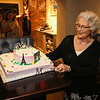 Ellie Whitney admires a decorated cake wishing her well with figures depicting her planned travels to Paris where she's going to go biking and sightseeing on Monday at the Tinos Greek Kitchen/Galley Hatch Restaurant to celebrate her retirement after 44 years at the Galley Hatch on 4-30-2018, Hampton, NH.  Matt Parker Photos