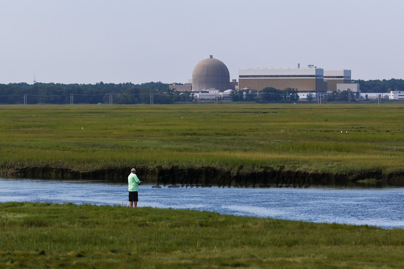 Fishing in the Seabrook-Hamptons Estuary with Seabrook Nuclear Power Plant in the background on Sunday 8-26-2018 at Hampton Beach, NH.  Matt Parker Photos