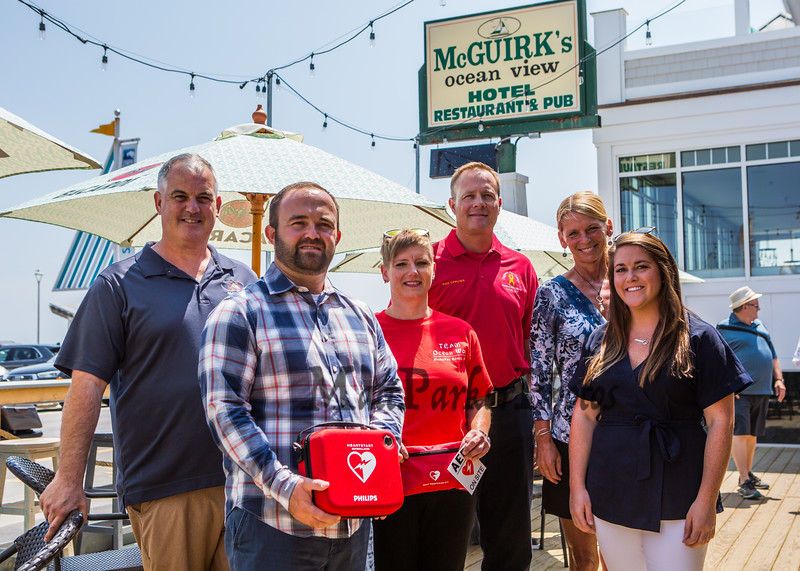 (L to R) Tom McGuirk of McGuirk's Restaurant, Tom Hunt Junior, Jessica Dolmat of Ocean Wok Restaurant, Nate Denio and EMS Officer of the Hampton FD, Kristen Gallant of CF Medical and Julie Hunt, The Hunt's mom Aideen donated an AED Defibrillator to McGuirk's and Ocean Wok restaurants after her husband Tom Hunt died of cardiac arrest, photo taken on Friday 8-2-2019, Hampton Beach, NH.  [Matt Parker/Seacoastonline]