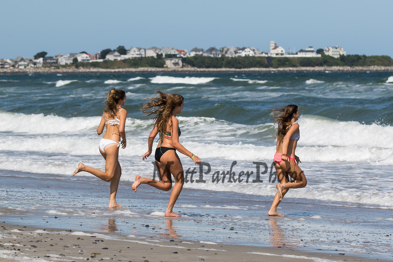 Three girls running into the surf in their bikins on Hampton Beach (L to R) Daniela Dinitto, Brooke Brown and Deanna Dinitto of Methuen and Melrose Mass on on a cool, windy and sunny Sunday 8-25-2019, Hampton Beach, NH.  Matt Parker Photos