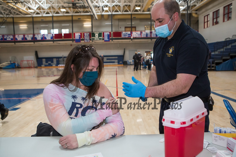WHS Cheerleading Coach Kally Keefe gets her COVID-19 vaccine from Hampton's Fire and Rescue Gary Lemoine as Teachers, Administrators and Staff from local area seacoast schools get their first dose of the COVID-19 vaccine at Winnacunnet High School, Hampton NH on Saturday March 20th, 2021.  Matt Parker Photos
