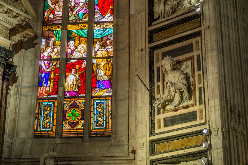 Stainglass and sculpture inside the Duomo di Milano.