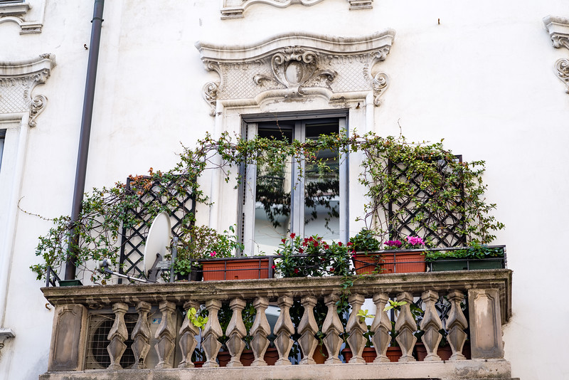 Almost every balcony has flowers in Milan, and maybe even a TV satellite disk.