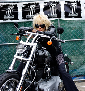 "Rock singer, Michael Monroe, straddles a Harley-Davidson motorcycle at ""Harley-Davidson Does SXSW"" in Austin, Texas."