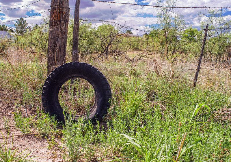 Old, dicarded truck tire among a tangle of fencing wire and weeds.