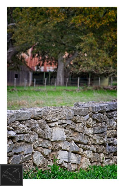 Stone wall, ranch house and rusted roof.