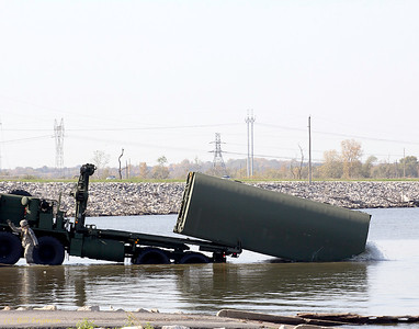 The released bridge section rolls off the transport into the water.  The wet soldier wades back to shore.