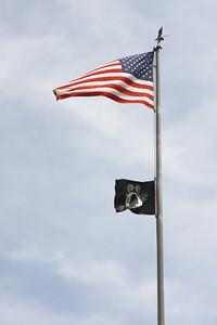 A US flag flying above a POW-MIA flag