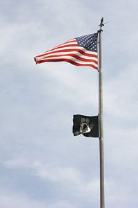 A US flag flying above a POW-MIA flag
