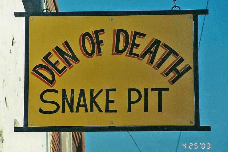 """In downtown Waynoka, they have an old storefront that has a wooden walled area just filled with rattlesnakes of all shapes and sizes.  Leaning over the wall and peering into that pit of rattlers was """"interesting"""" enough.  But also, in that pit, were 3 guys walking around amongst those rattlers trying to entice them to strike at their boots, etc.  They would pick them up with hooks - or sometimes their hands - to show us standing round the pit various traits and features of the snakes."""