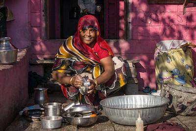 dappled woman with nice smile washing pots