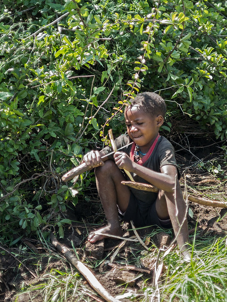 Hadza boy with knife and stick