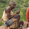 older Hadza man on rock with beer