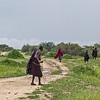 Maasai people walking on road to Yaea Valley
