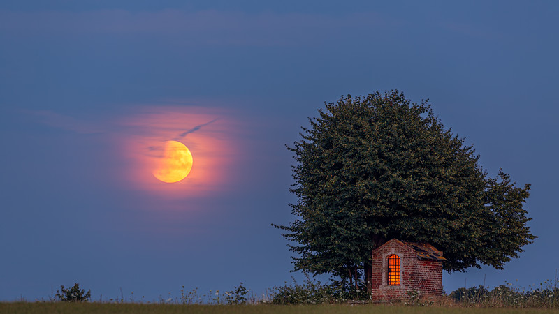 Partial lunar eclipse at the Saint Joseph Chapel under a centuries-old lime tree, Sint-Pieters-Rode (Horst), Belgium