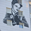 artwork on a building in Switzerland of Charlie Chaplin as the little tramp in the film modern times.