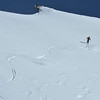 Skier in a glacial wilderness in fresh powder snow, leaving elegant tracks.