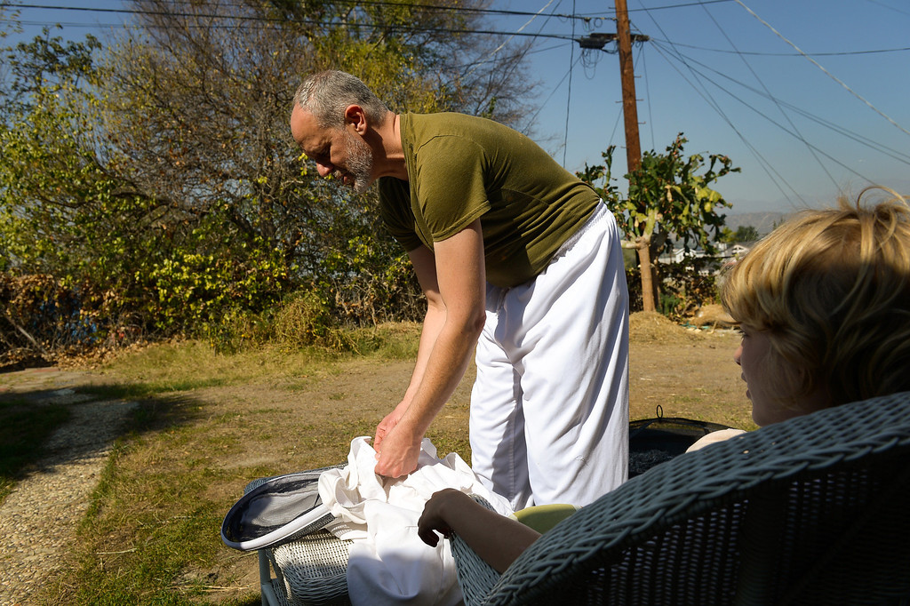 . David Bock puts on his bee suit in the backyard of his Glassell Park home while his son, Leo, 10, watches, Tuesday, February 25, 2014. (Photo by Michael Owen Baker/L.A. Daily News)