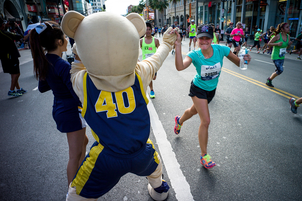 . A runner gets a high five from a bear along Hollywood blvd in Hollywood during the 29th Los Angeles Marathon Sunday, March 9, 2014.   (Photo by David Crane/Los Angeles Daily News.)